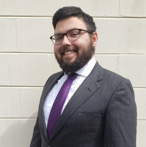 Jorge Alvarez in a black suit with a purple tie. Jorge stands in front of a white wall.