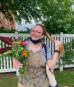 India stands in a backyard patio wearing a pair of tan overalls over a gray shirt. She is wearing glasses. Her right hand holds a small bouquet of flowers and her left hand holds a length of her blond hair. Behind her is a tall white metal fence.